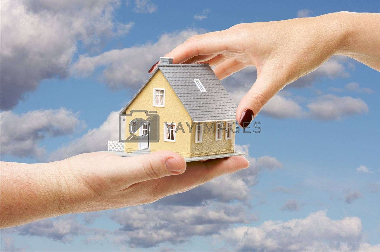 Female hand reaching for a house on a partly cloudy sky background.