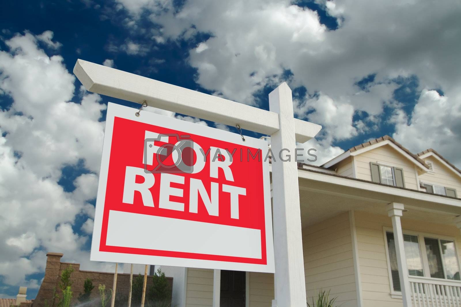 For Rent sign in front of new home with dramatic Blue Sky and clouds behind.