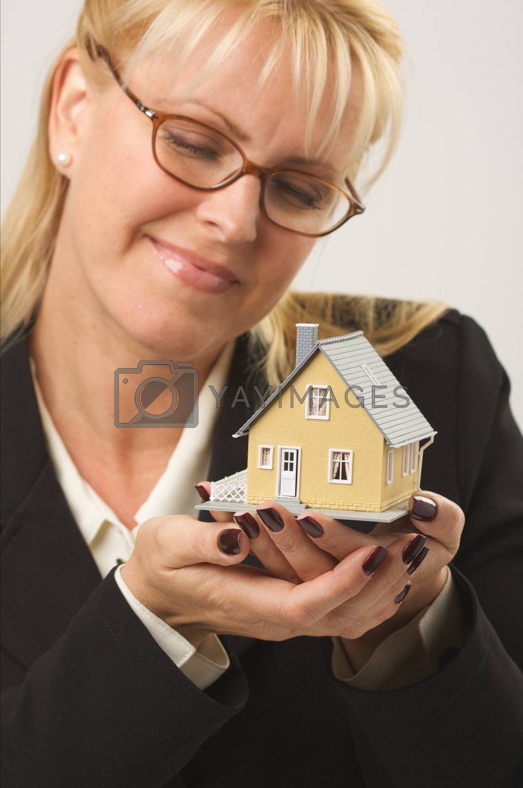 Female holding and looking at small house.