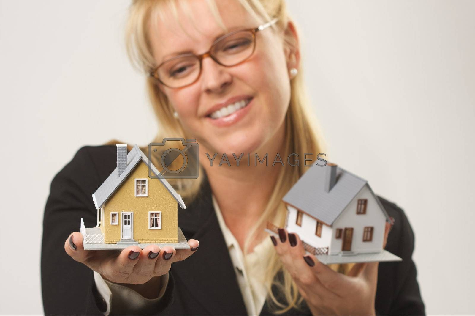 Female holding two houses contemplating each.