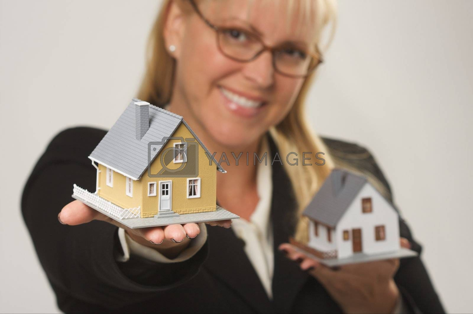 Female holding two houses and presenting one.