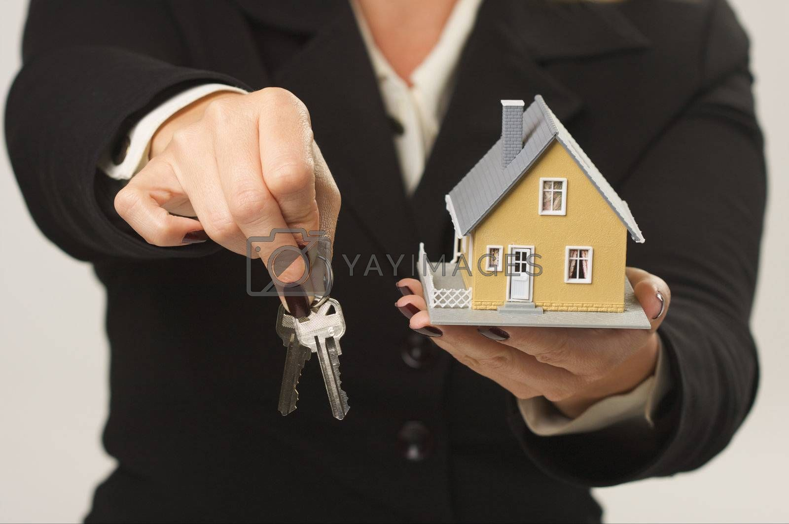 Female presenting keys and small house.