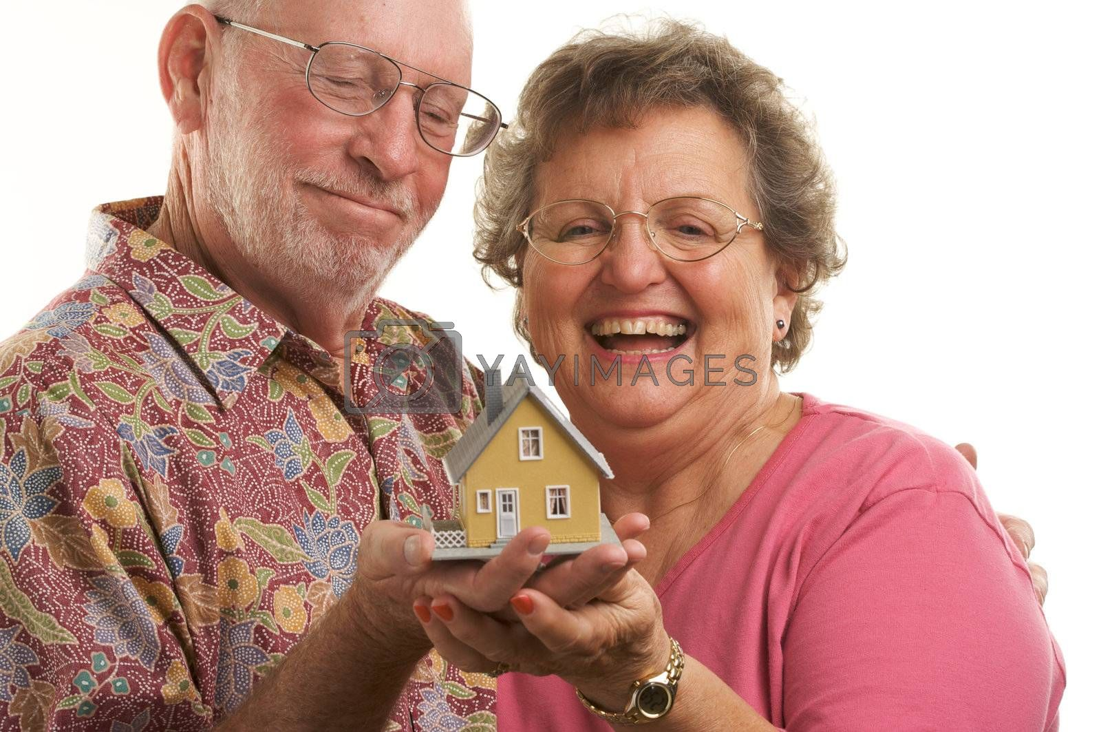 Happy Senior Couple holding a model home.