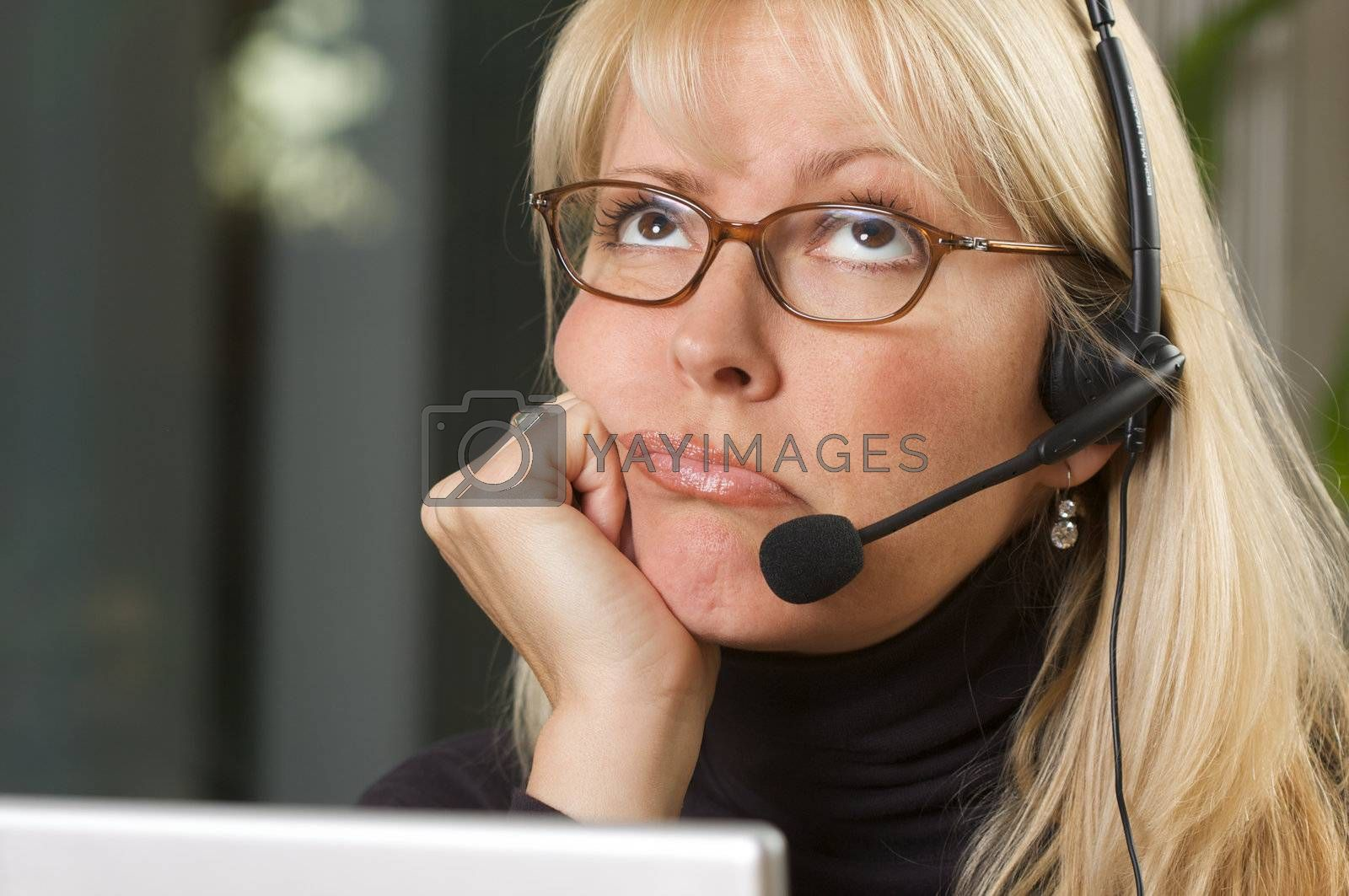 Attractive businesswoman talks on her phone headset.