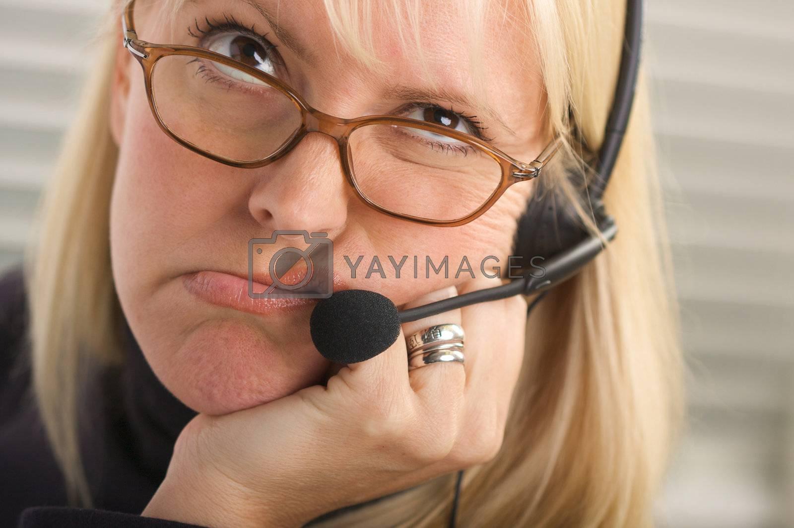 Attractive businesswoman talks on her phone headset.