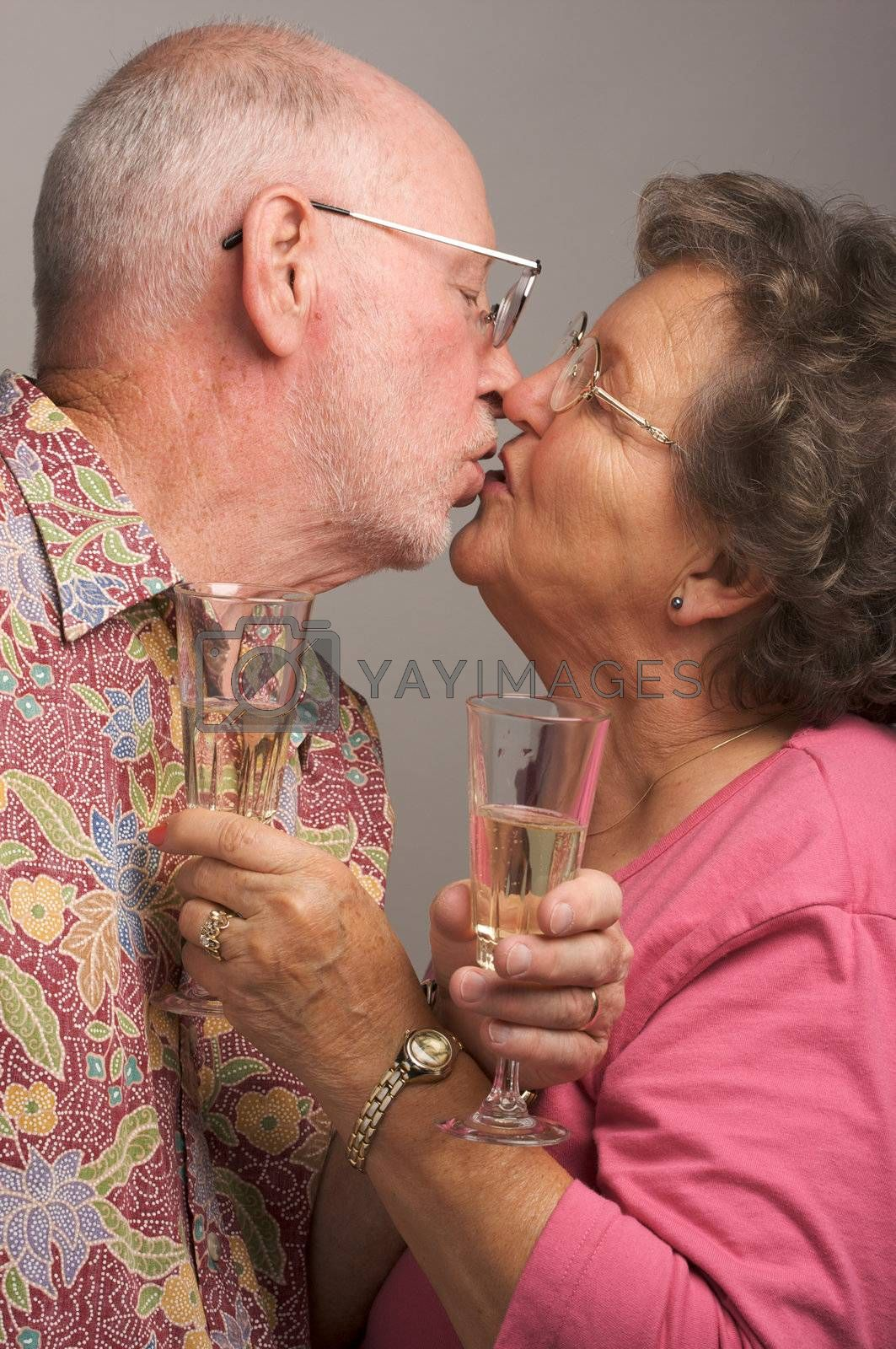 Happy Senior Couple Kissing while holding Champagne glasses.