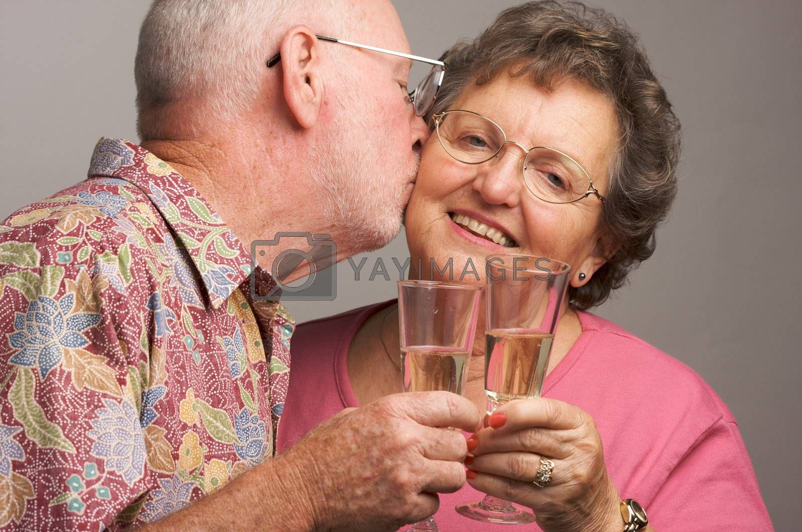 Happy Senior Couple toasting with Champagne glasses.