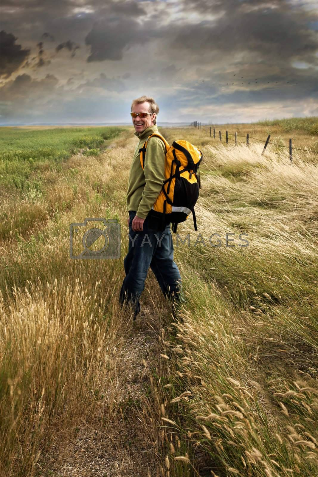 Man looking back and smiling on a prairie country road