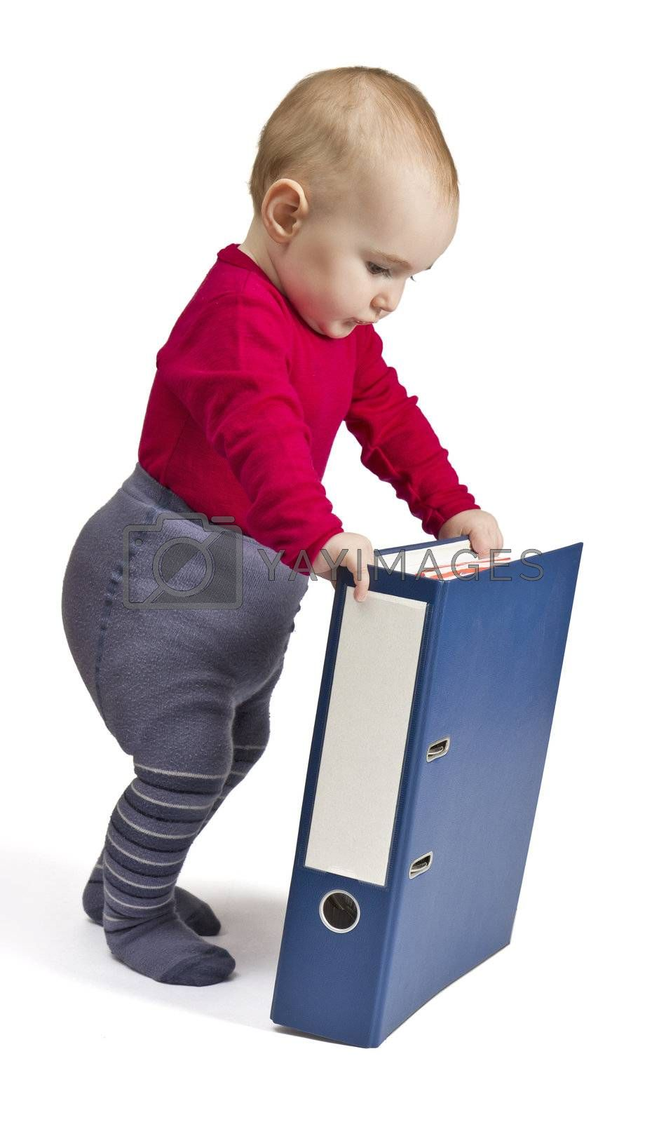 small child in red shirt standing next to blue ring binder. white background with shadow
