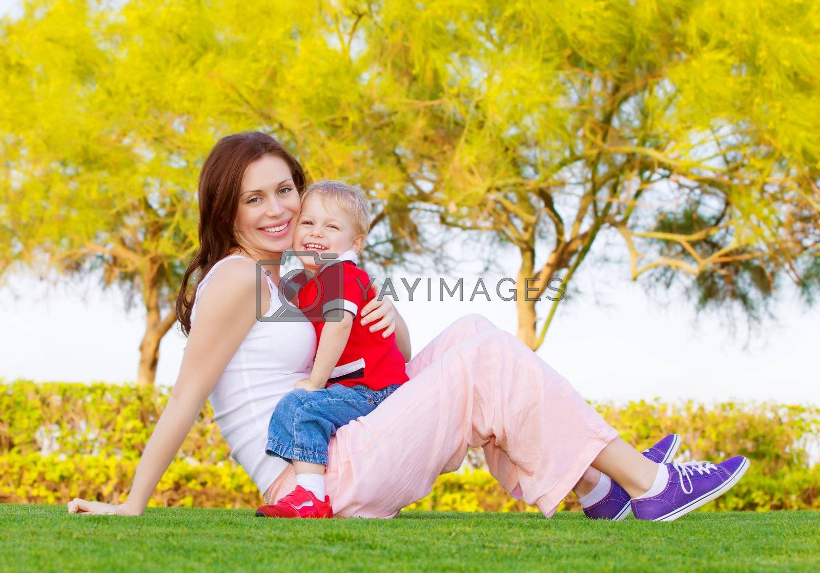 Picture of attractive woman with cute child sitting down on green grass in spring park, mother with son enjoying springtime nature, little boy with mom spending time outdoors, happy young family