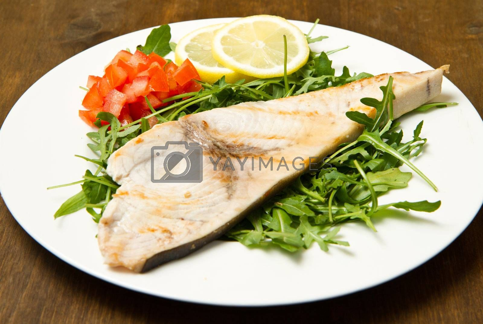 roasted swordfish with lemon, salad and tomatoes on wooden background