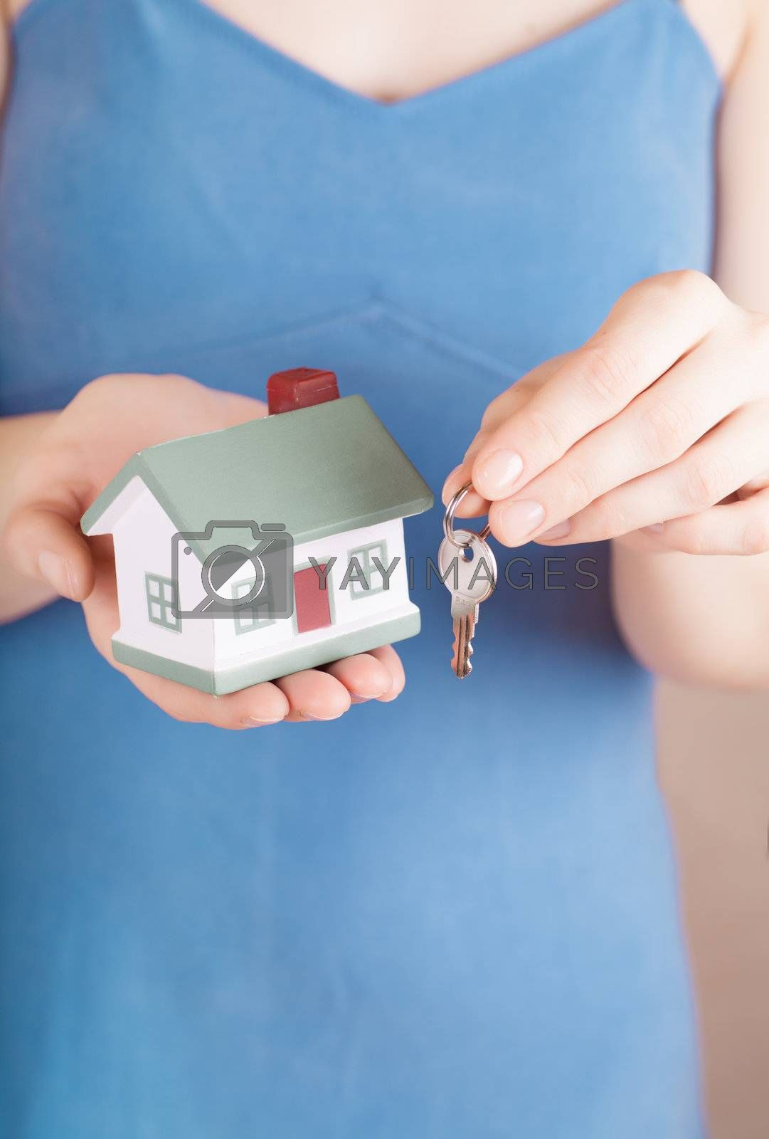 Little house toy and a key in woman hands