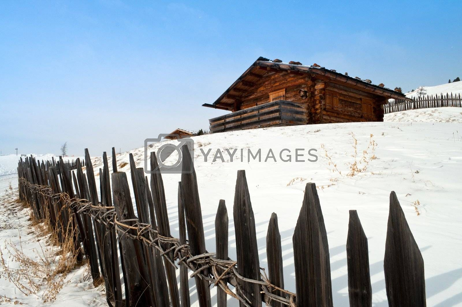 Old winter wood cottage with fence in Dolomiti Alps, Ortisei, italy.