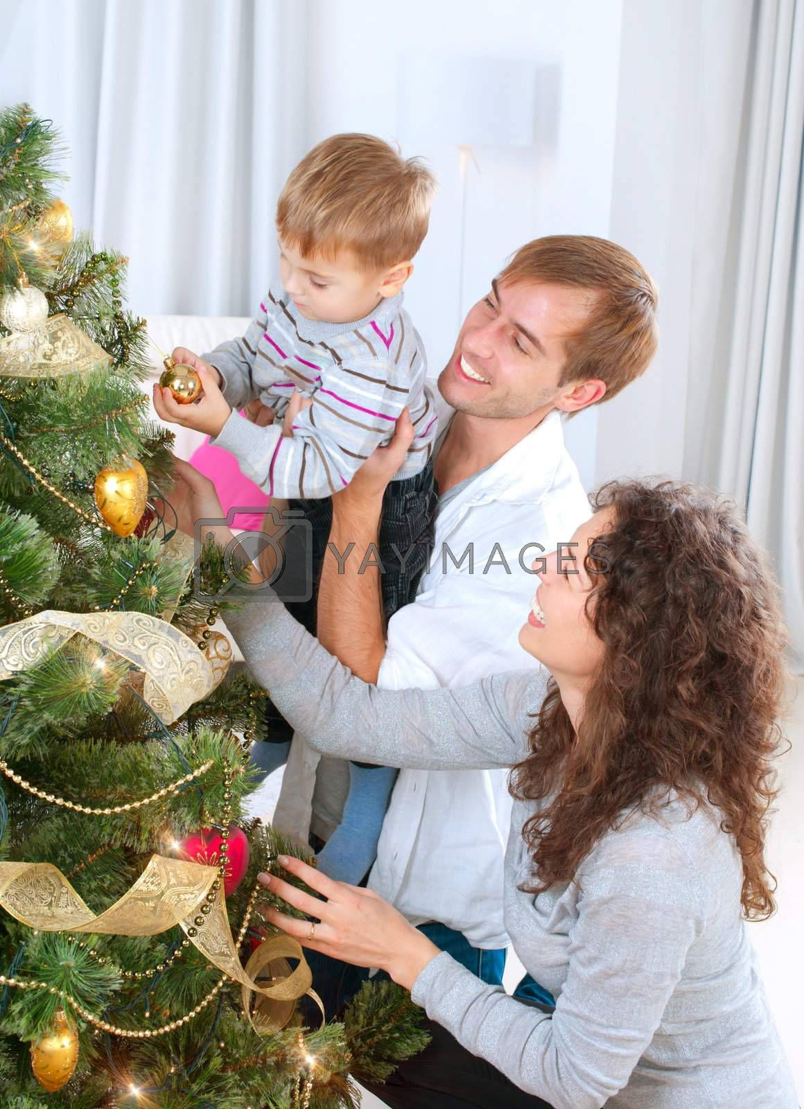 Young Family decorating a Christmas Tree	 by SubbotinaA