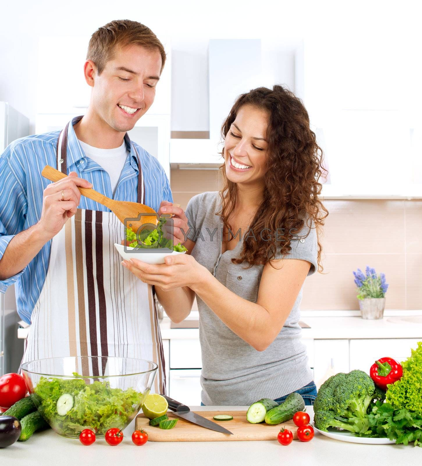 Young Man Cooking. Happy Couple Eating Fresh Vegetable Salad  by Subbotina Anna