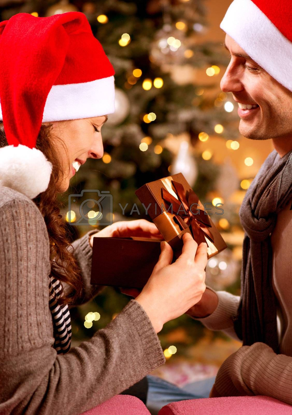 Christmas Scene. Happy Couple with Christmas Gift at Home  by Subbotina Anna