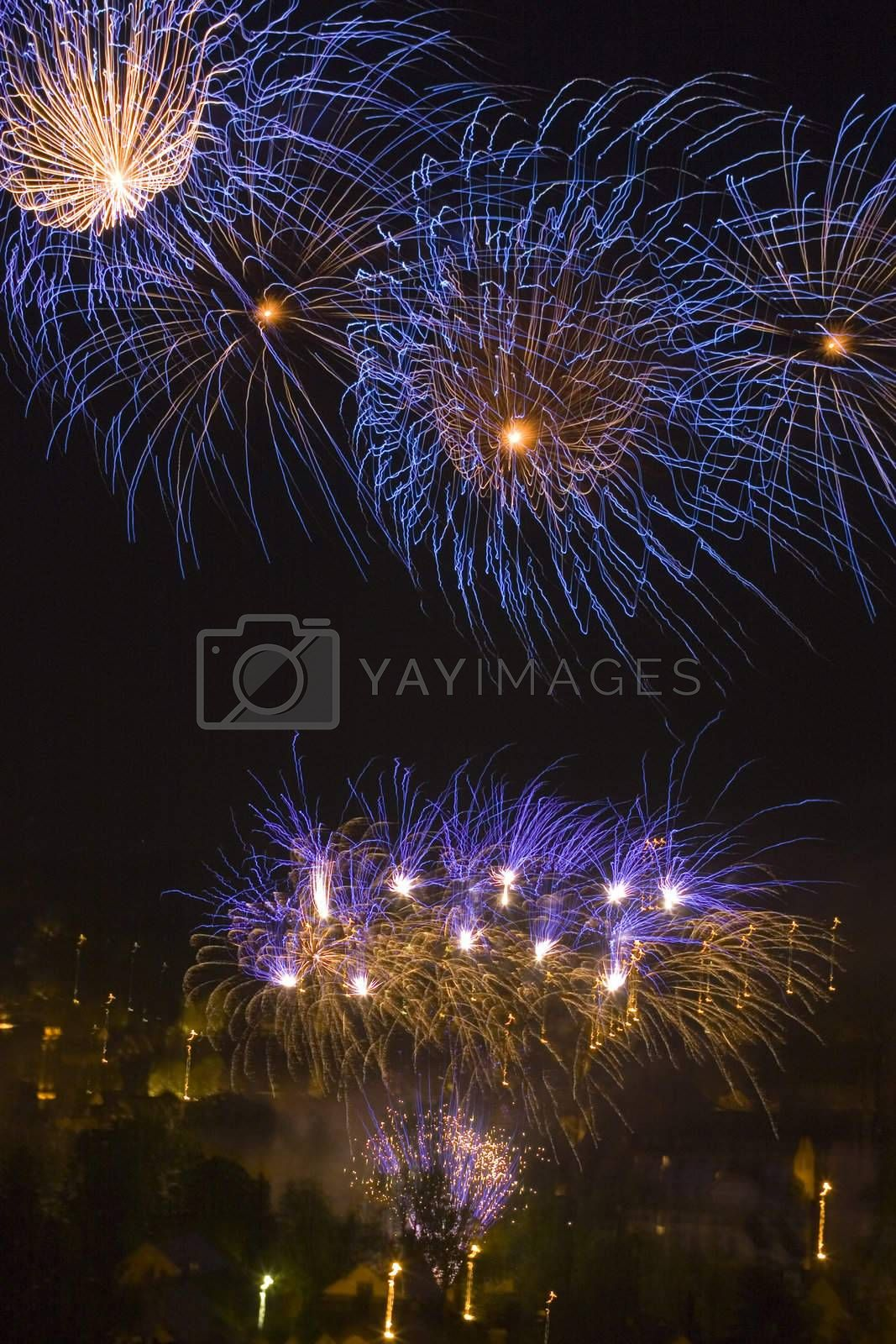 Colorful fireworks over a town by night