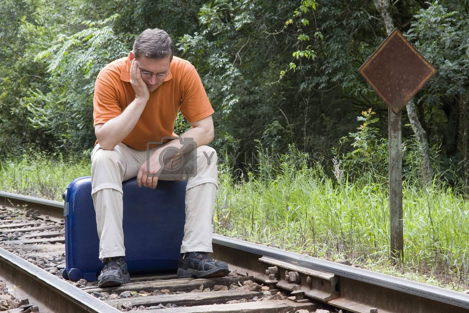 Tired man sitting on his suitcase on a railway
