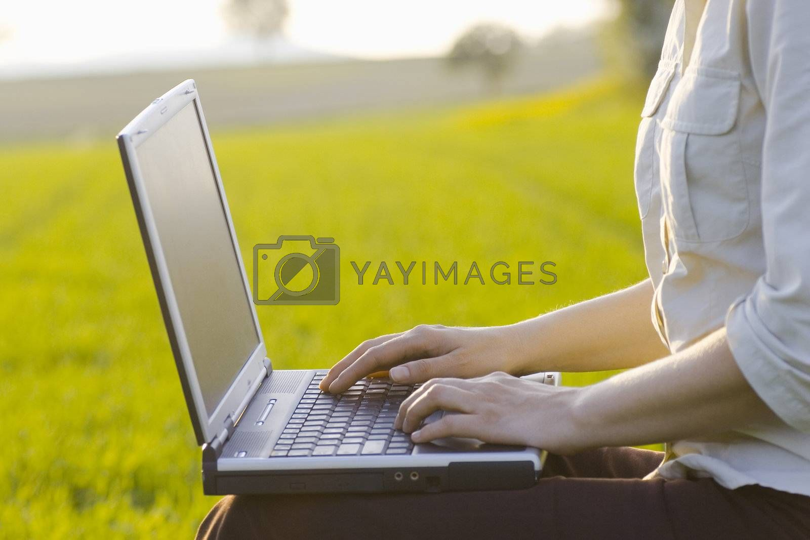 Woman typing on a laptop outside in a meadow. Focus only on the right hand.