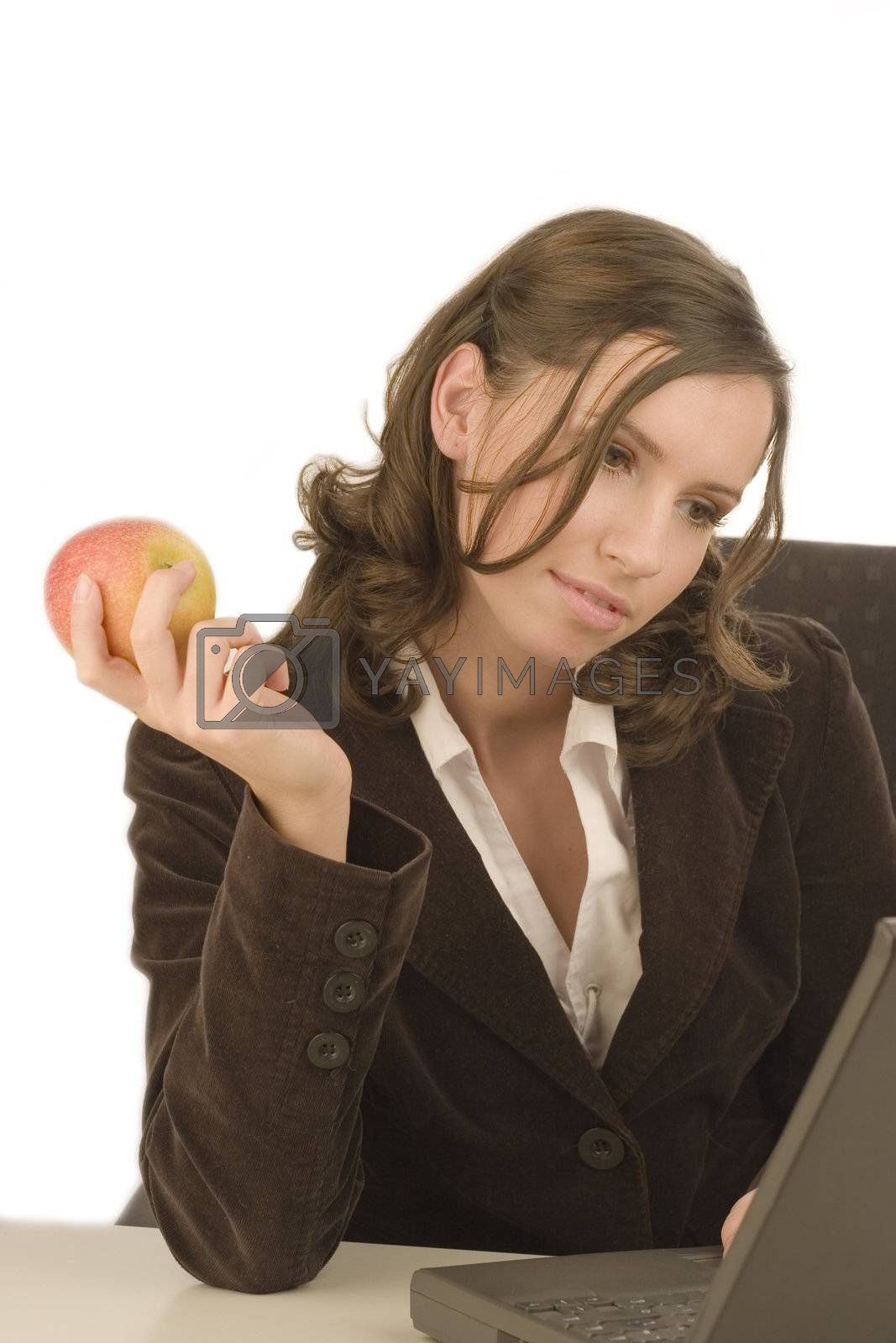 Young attractive woman looking at a laptop with an apple in her hand