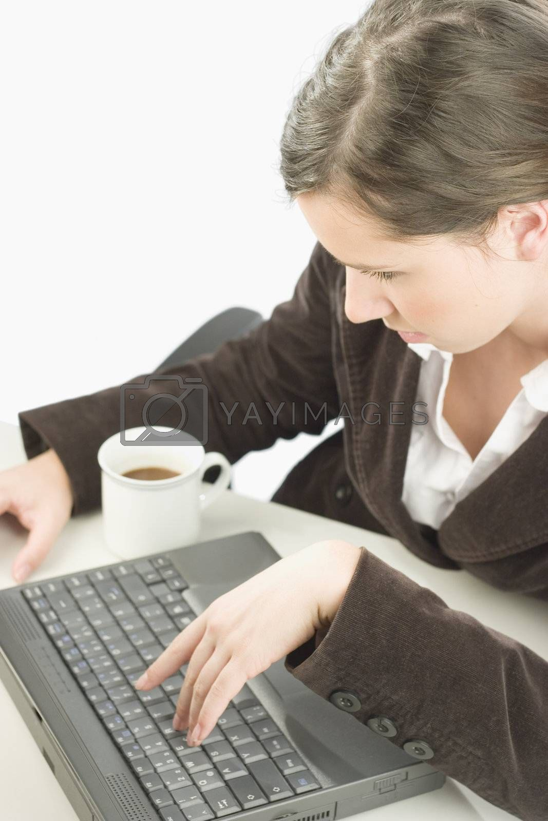 Tired business woman typing on the keyboard of a laptop with a cup of coffee by her side.