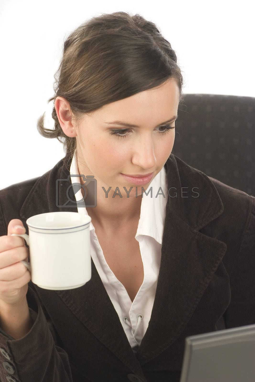 Young attractive woman with a cup of coffee in her hand looking at the screen of a laptop