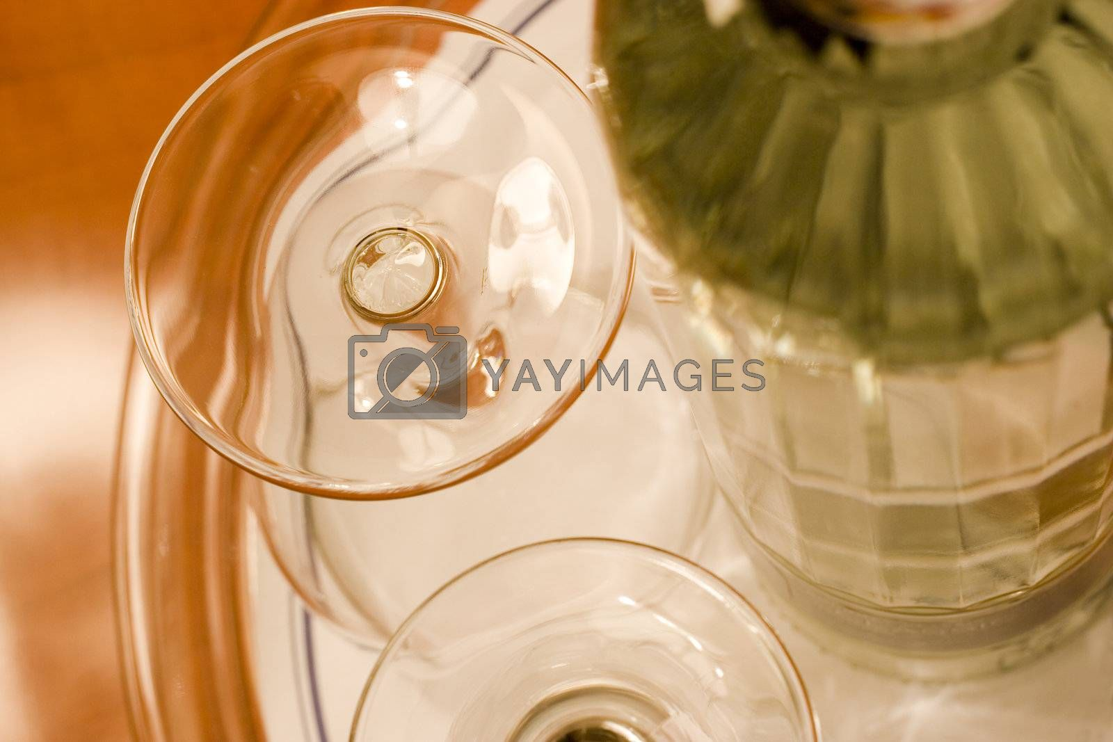 Two glasses and a bottle on a table of exotic woods. Focus on the top of the upper glass.