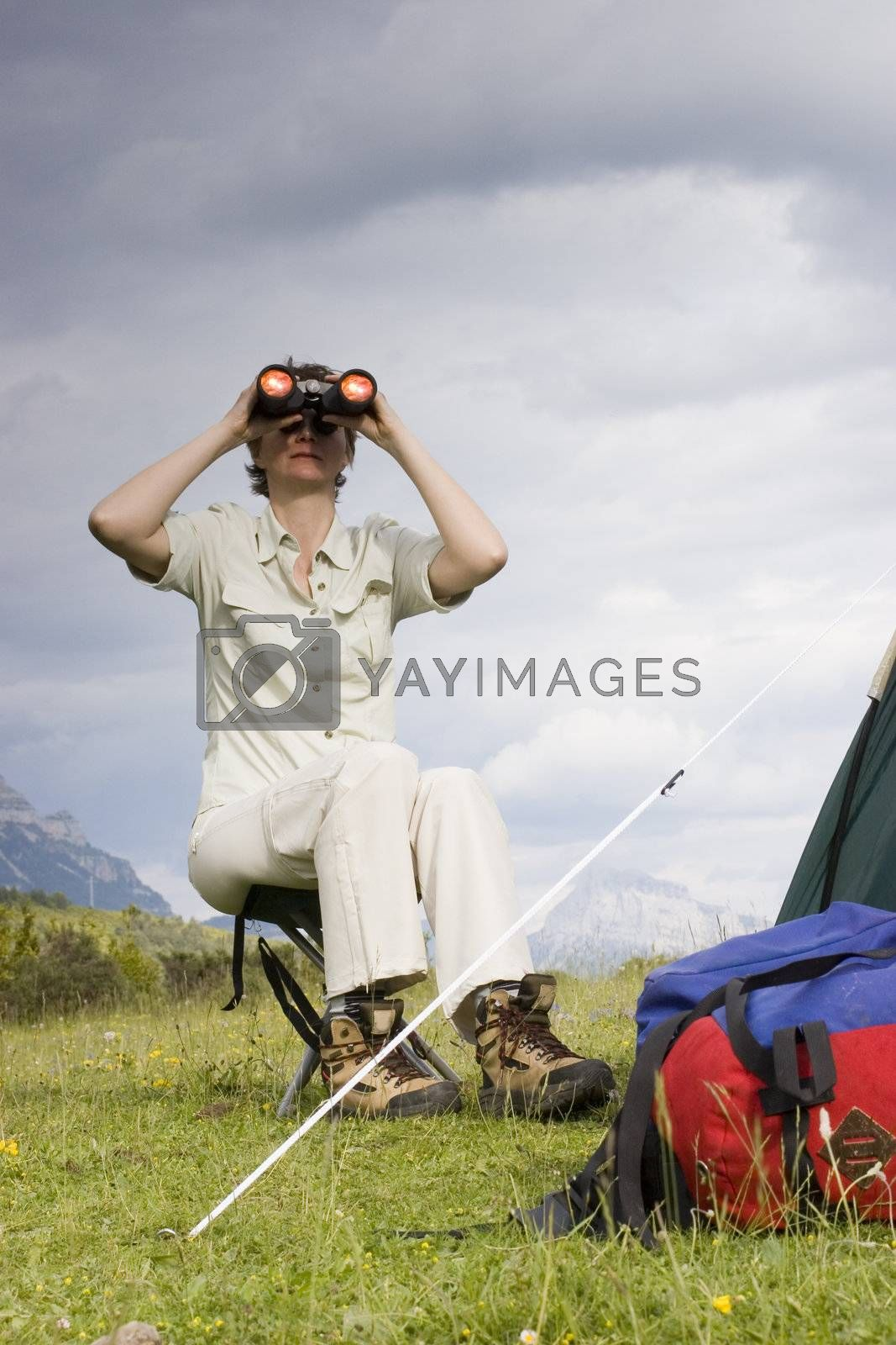 Woman looking through binoculars while sitting beside a tent in the mountains