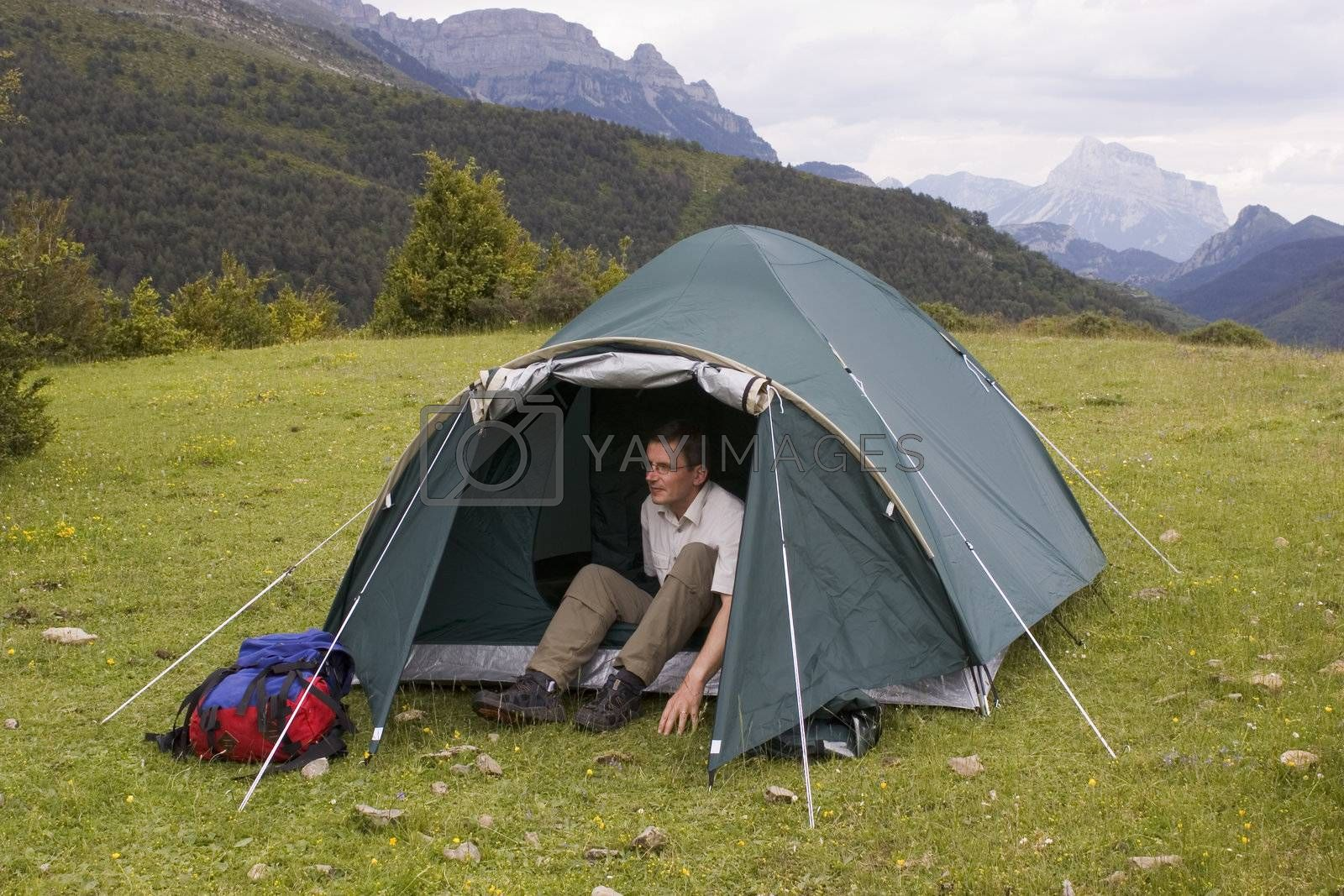 Mountaineer in his tent on a meadow with mountains in the background
