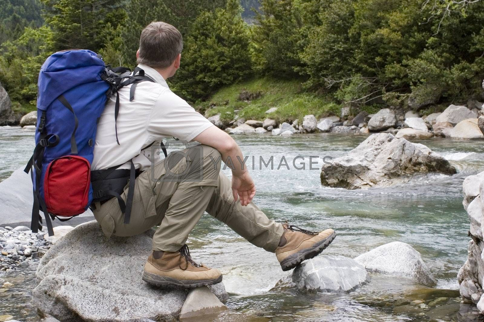 Hiker with backpack resting at a mountain river