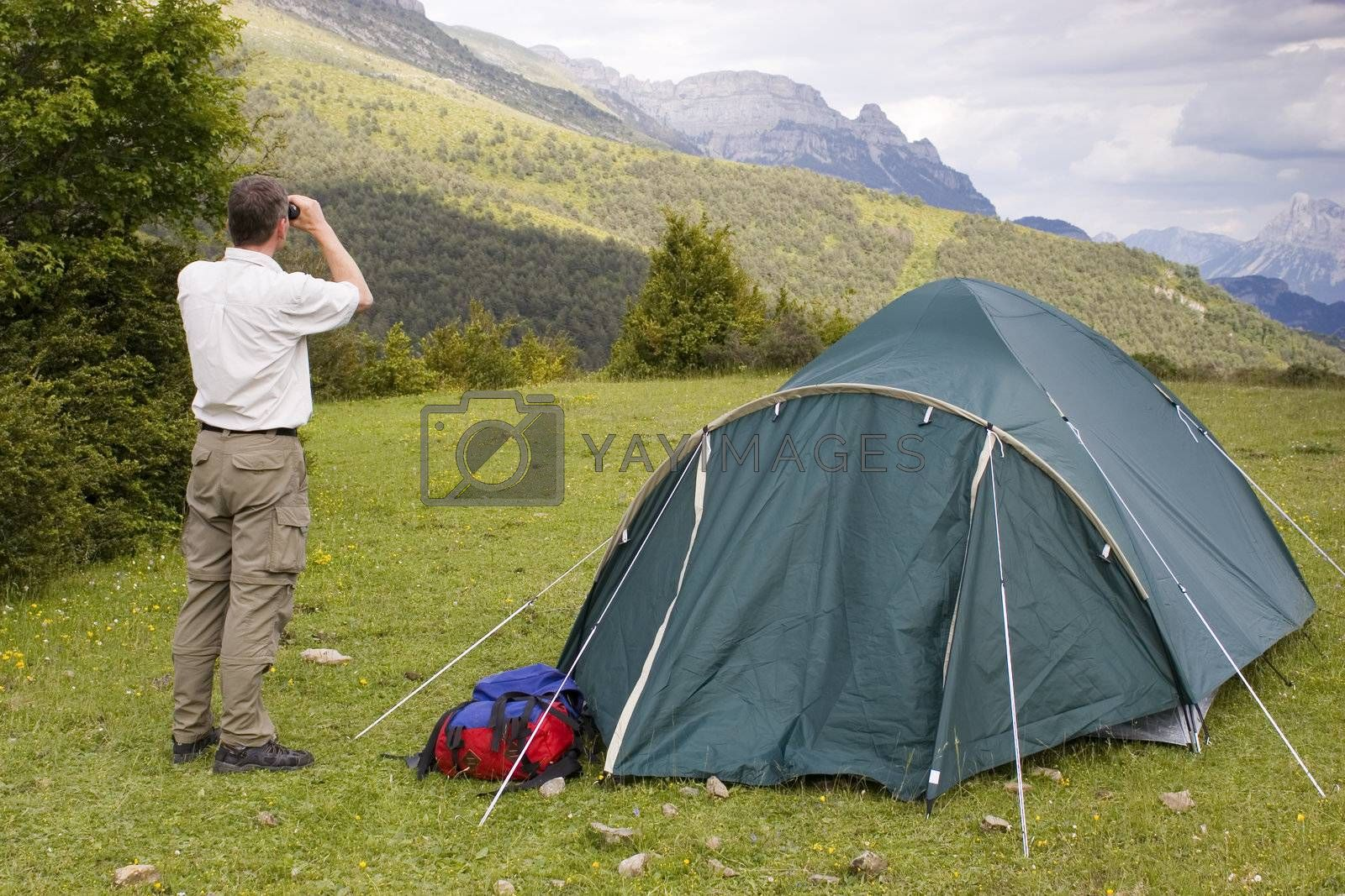 Mountaineer beside his tent looking with binoculars at the bad weather.