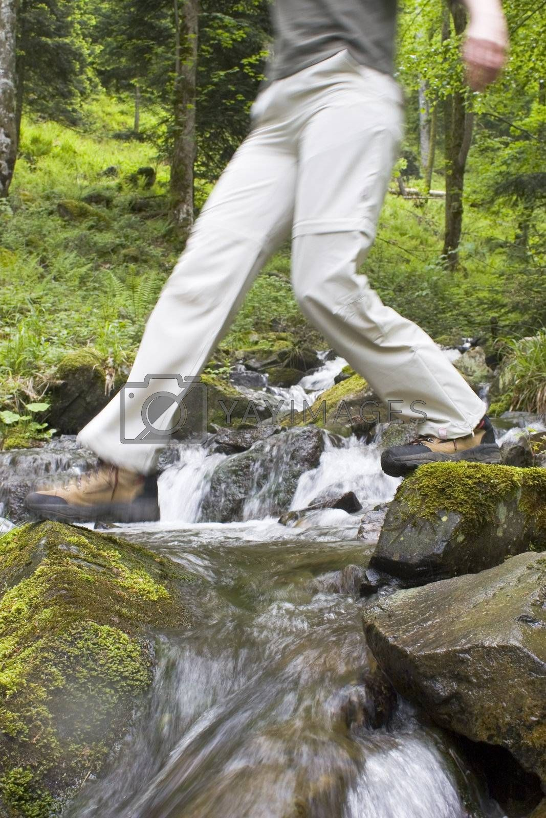 Hiking woman crossing a mountain creek