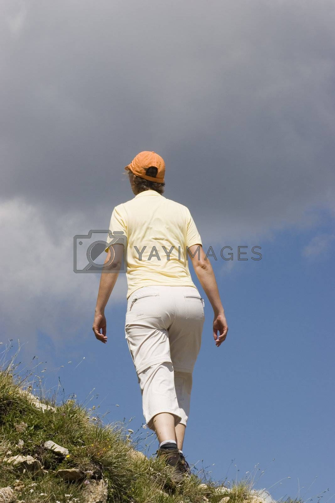 Woman hiking in the mountains against blue sky with clouds