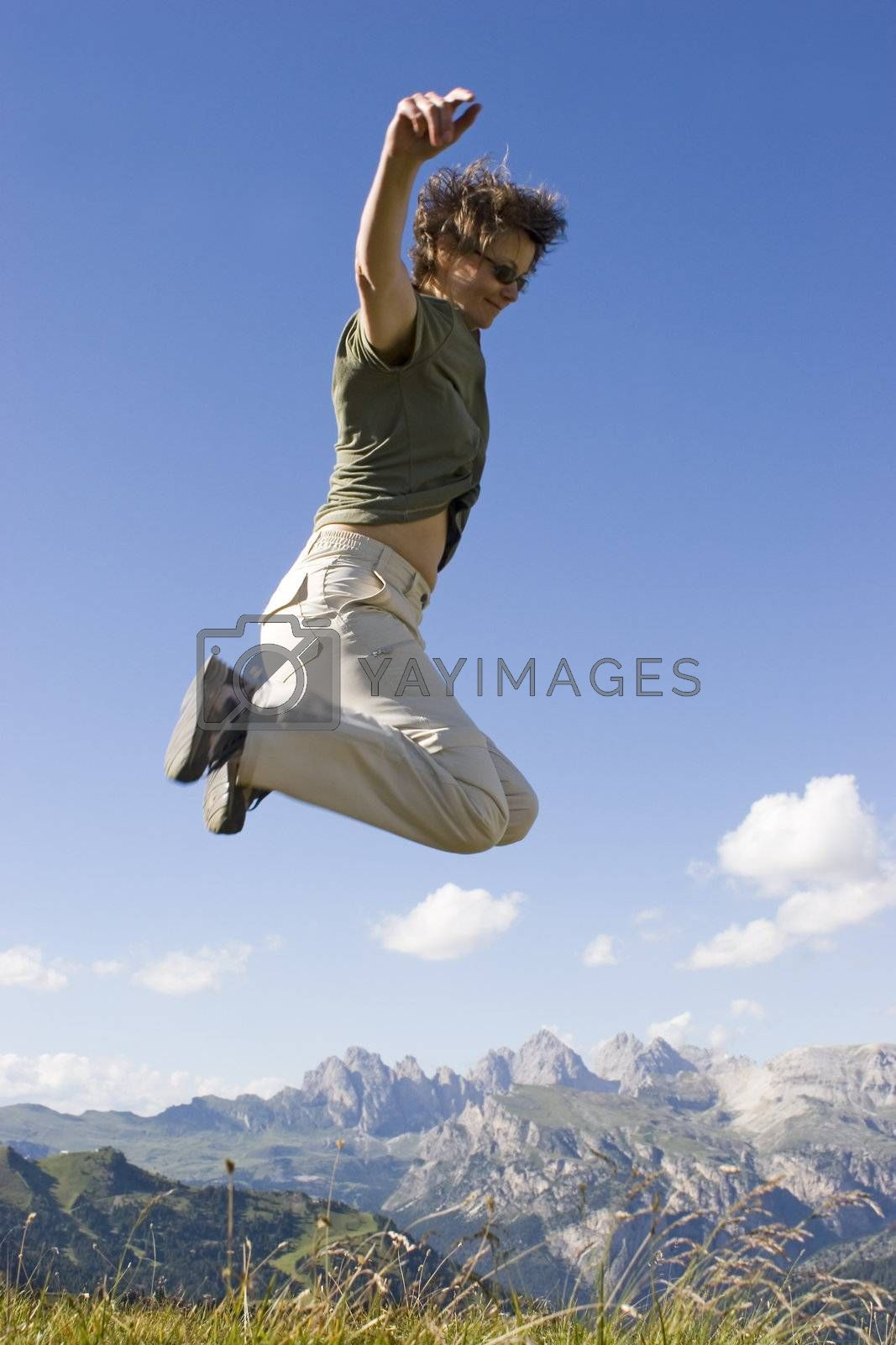 Real photo of a happy woman jumping in front of a mountain landscape. Partially motion blurred. Sella - Dolomites