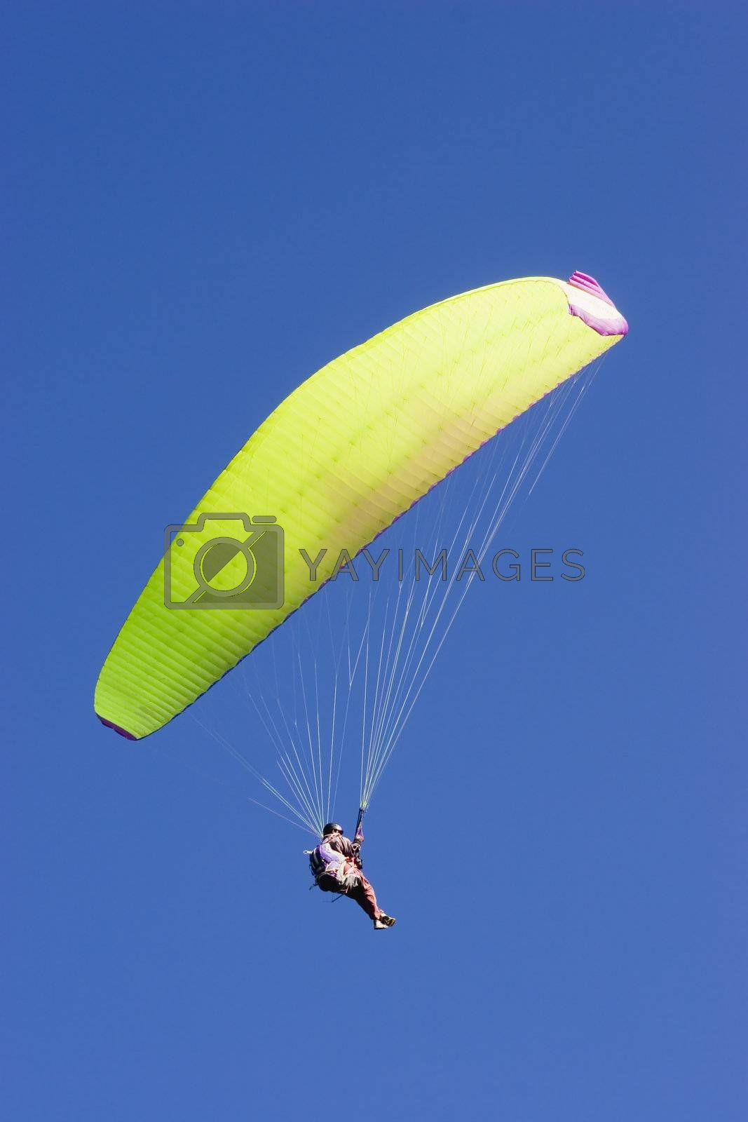 Yellow paraglider in a blue sky