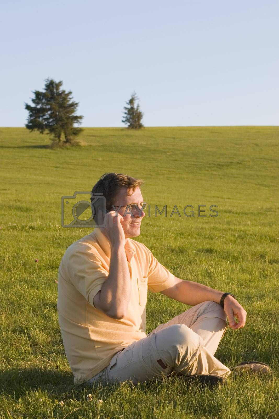 Man with cell phone talking while sitting in a meadow at sunset/sunrise