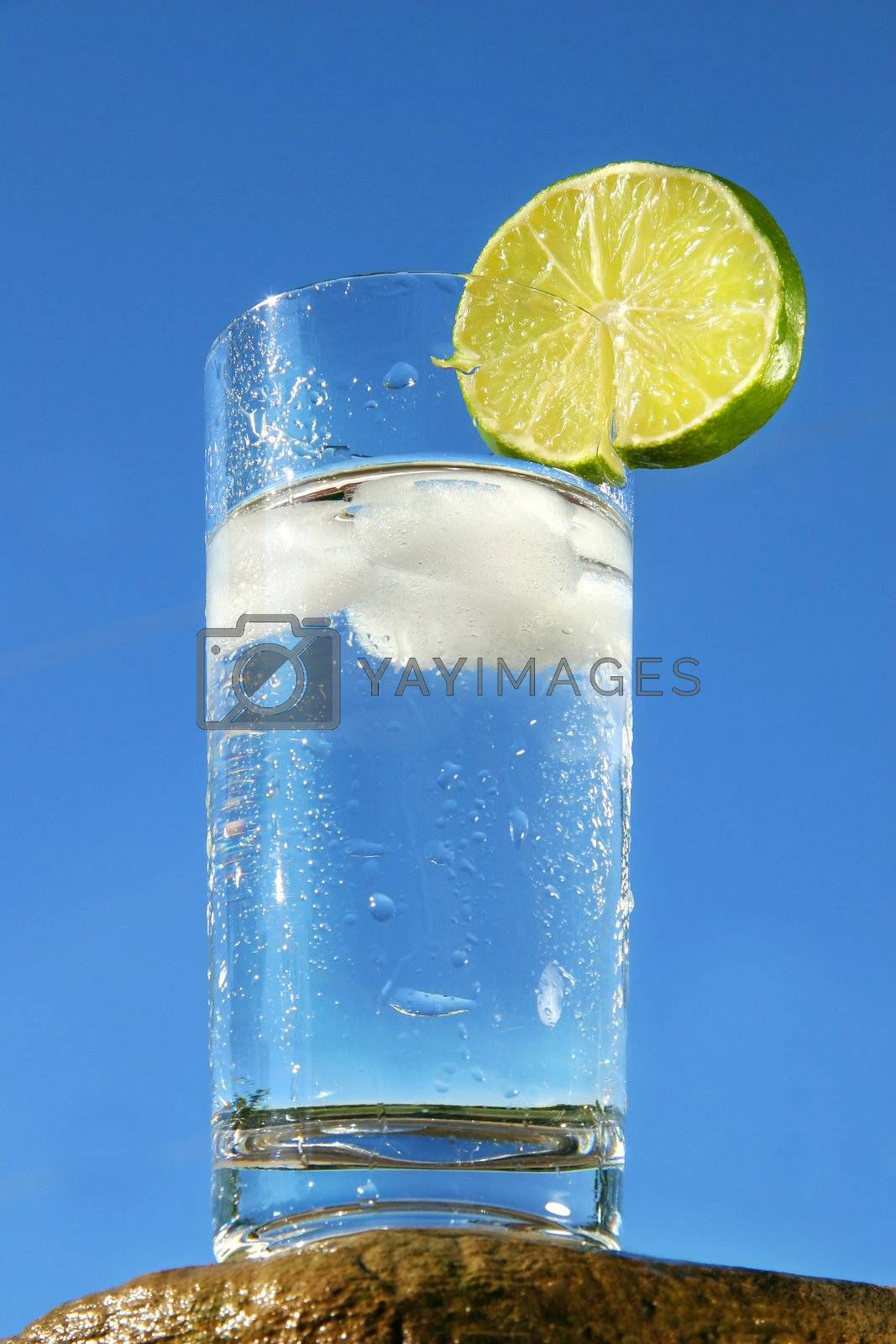 Cold glass of water against a blue sky by Sandralise
