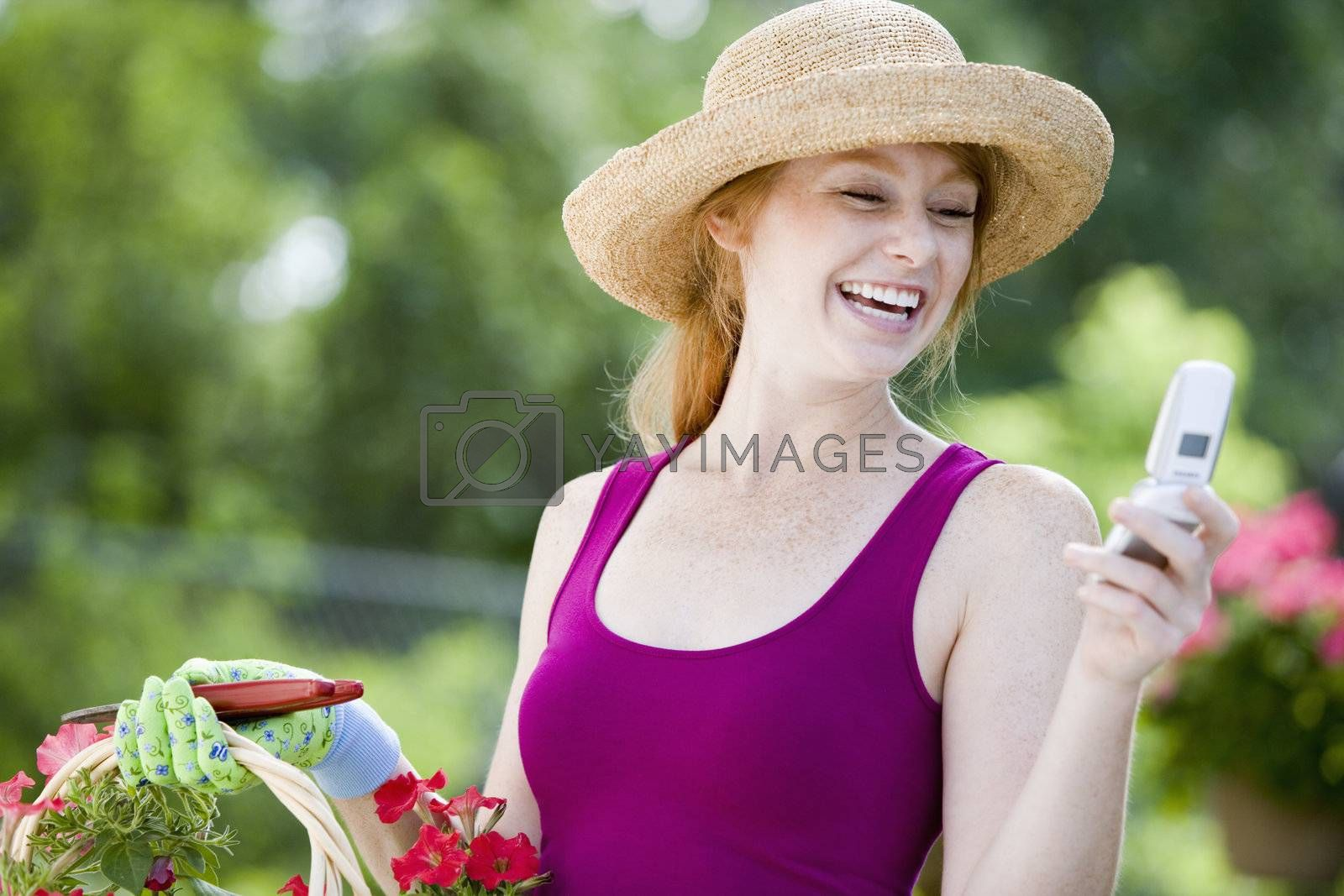 Laughing woman gardener looking at her cell phone