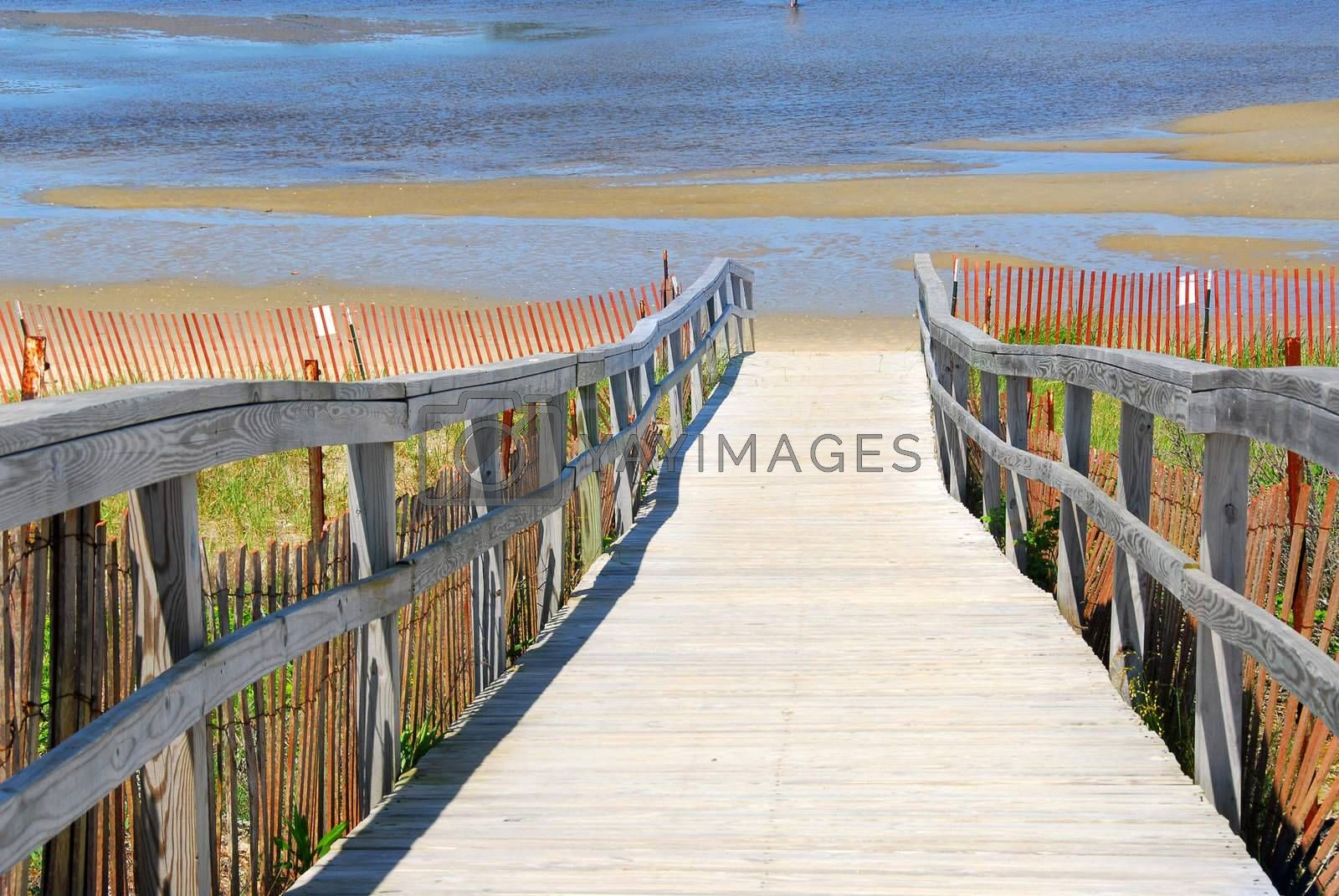 Wooden path over sand dunes with beach view