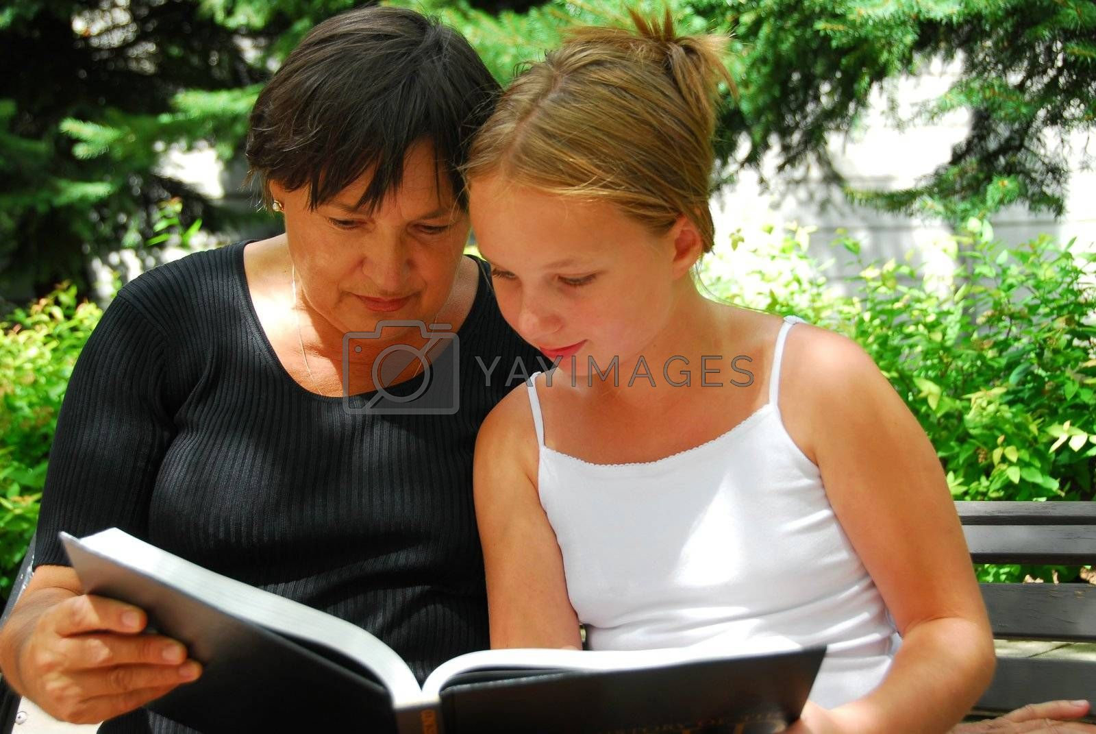 Grandmother and granddaughter reading a book