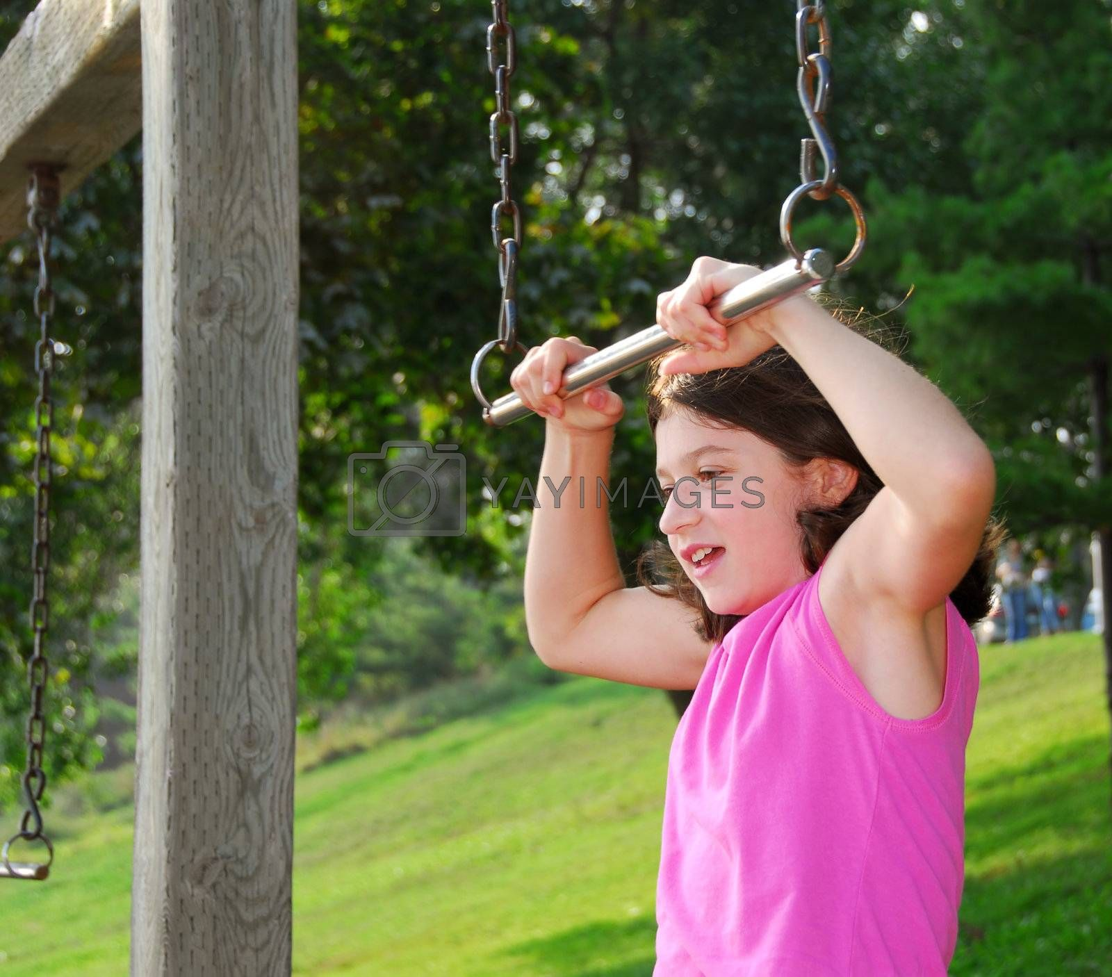 Portrait of a young girl playing on a playground at summertime