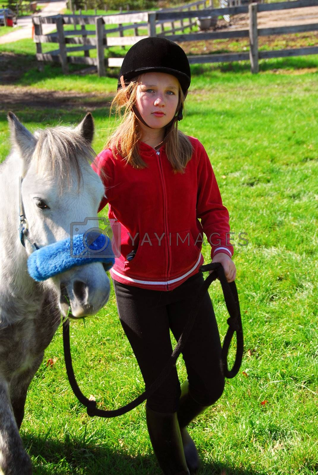Young girl leading her pony out to pasture