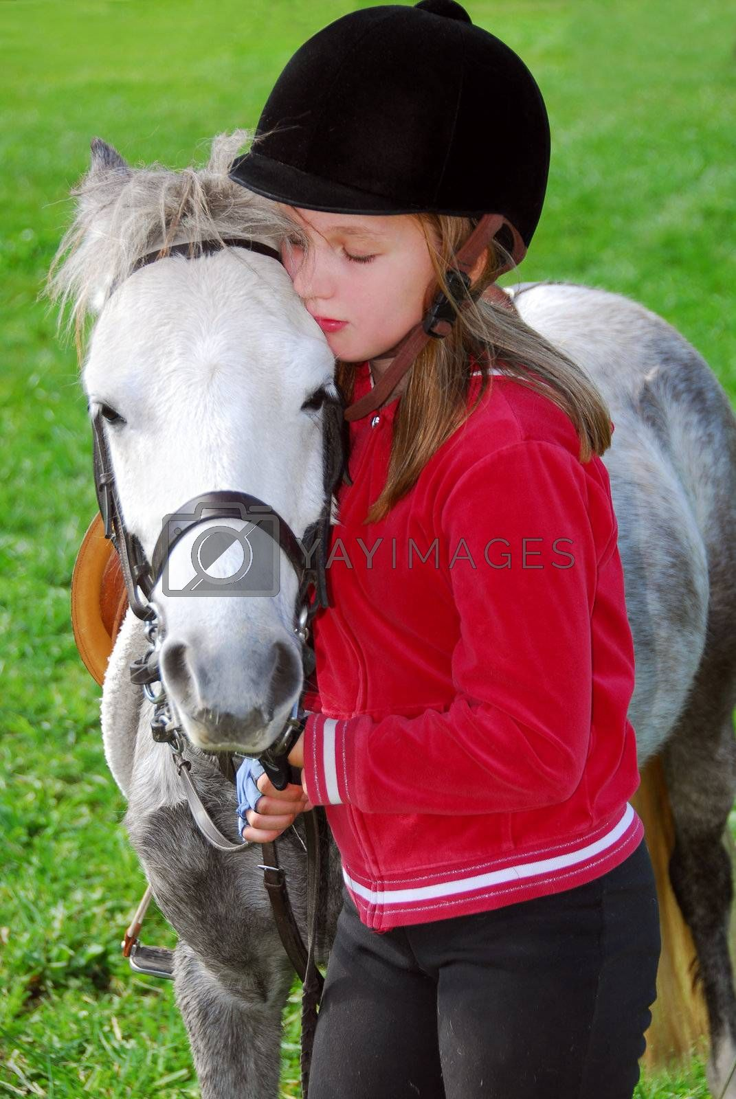Young girl with a white pony at countryside