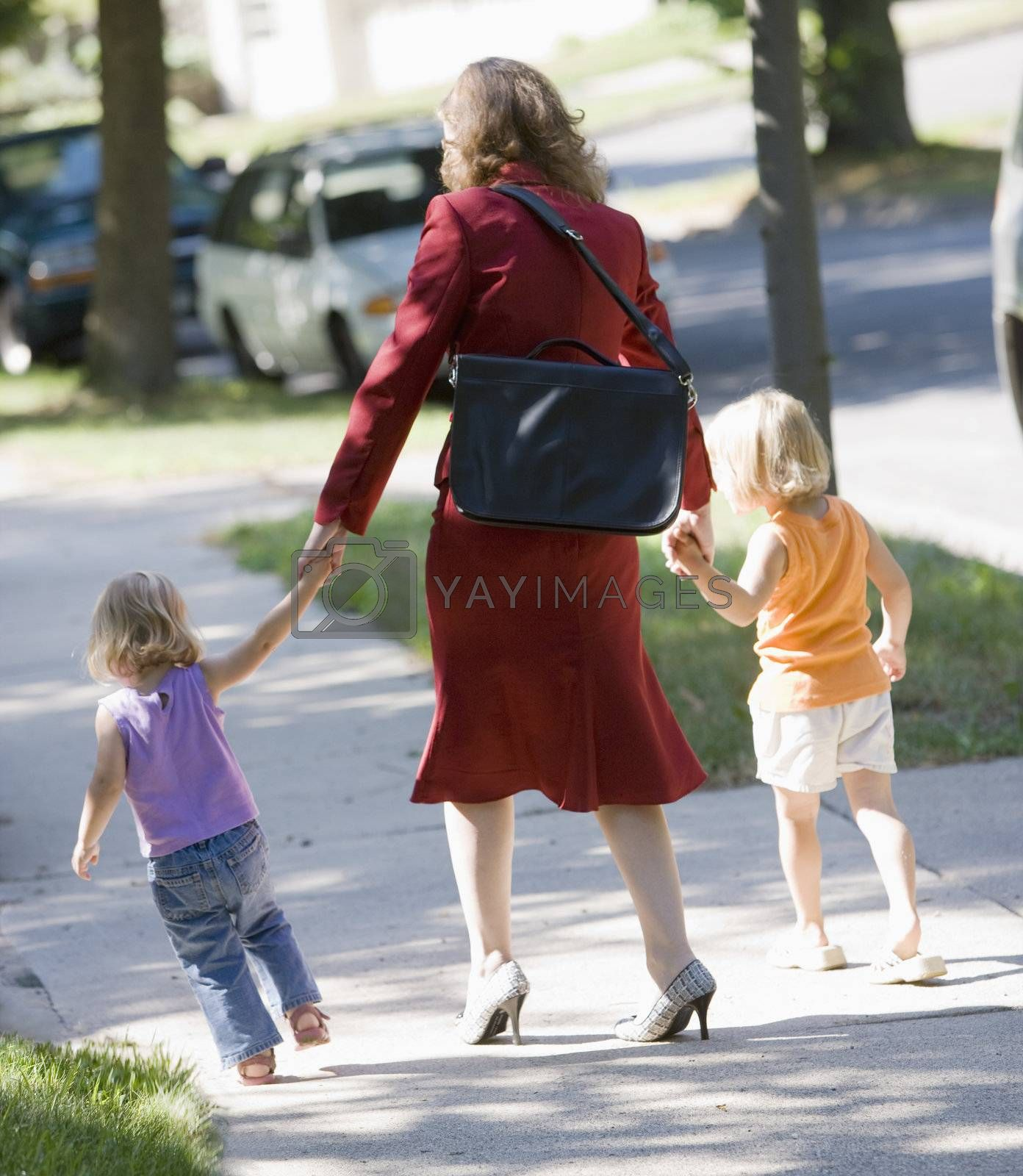 Professional woman walking her children to school or daycare