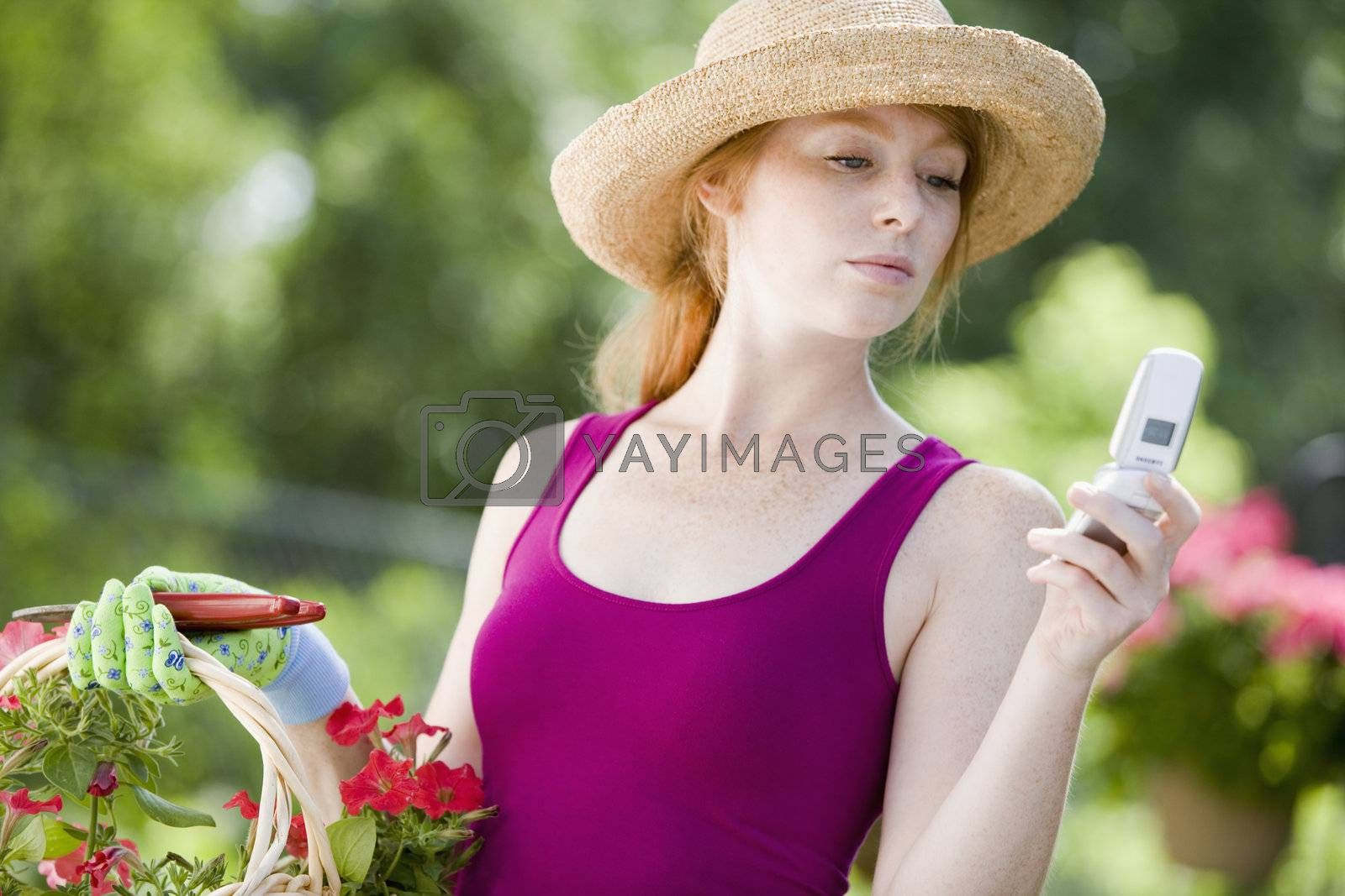 Pretty young woman gardener looking at her cell phone