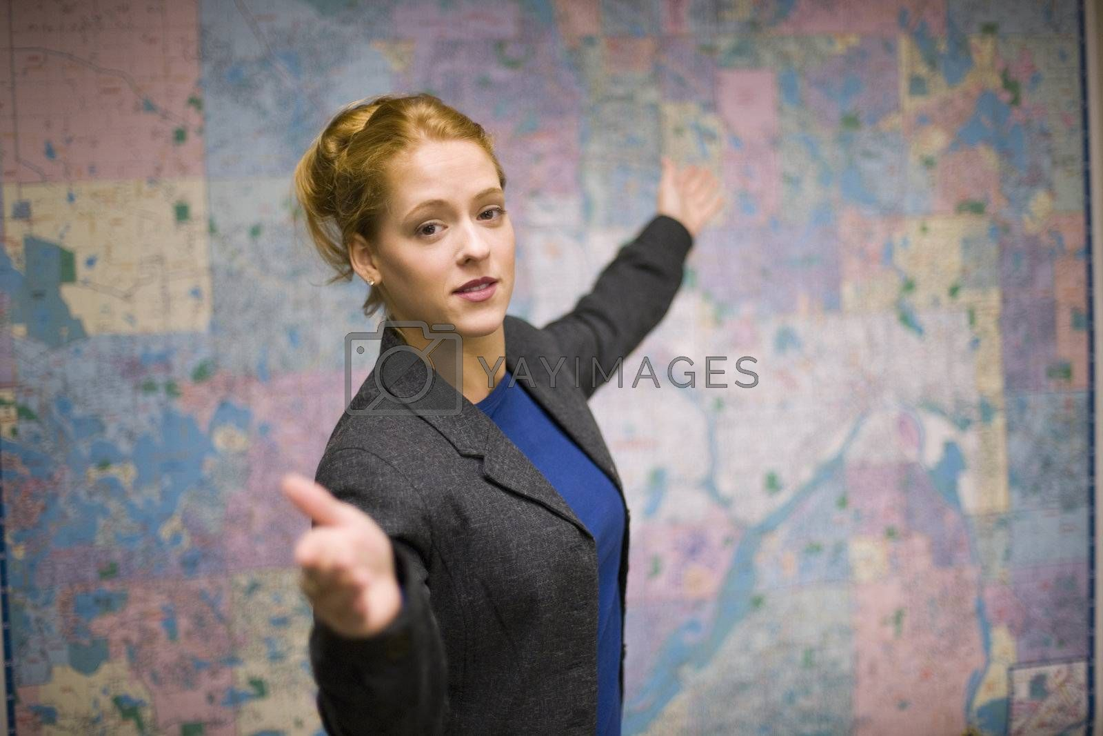 Young woman giving real estate presentation with map