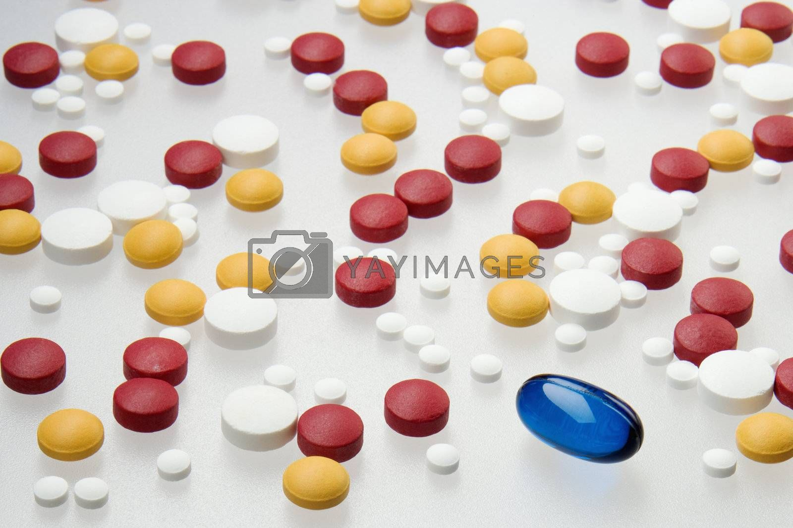 One large blue capsule among other smaller pills