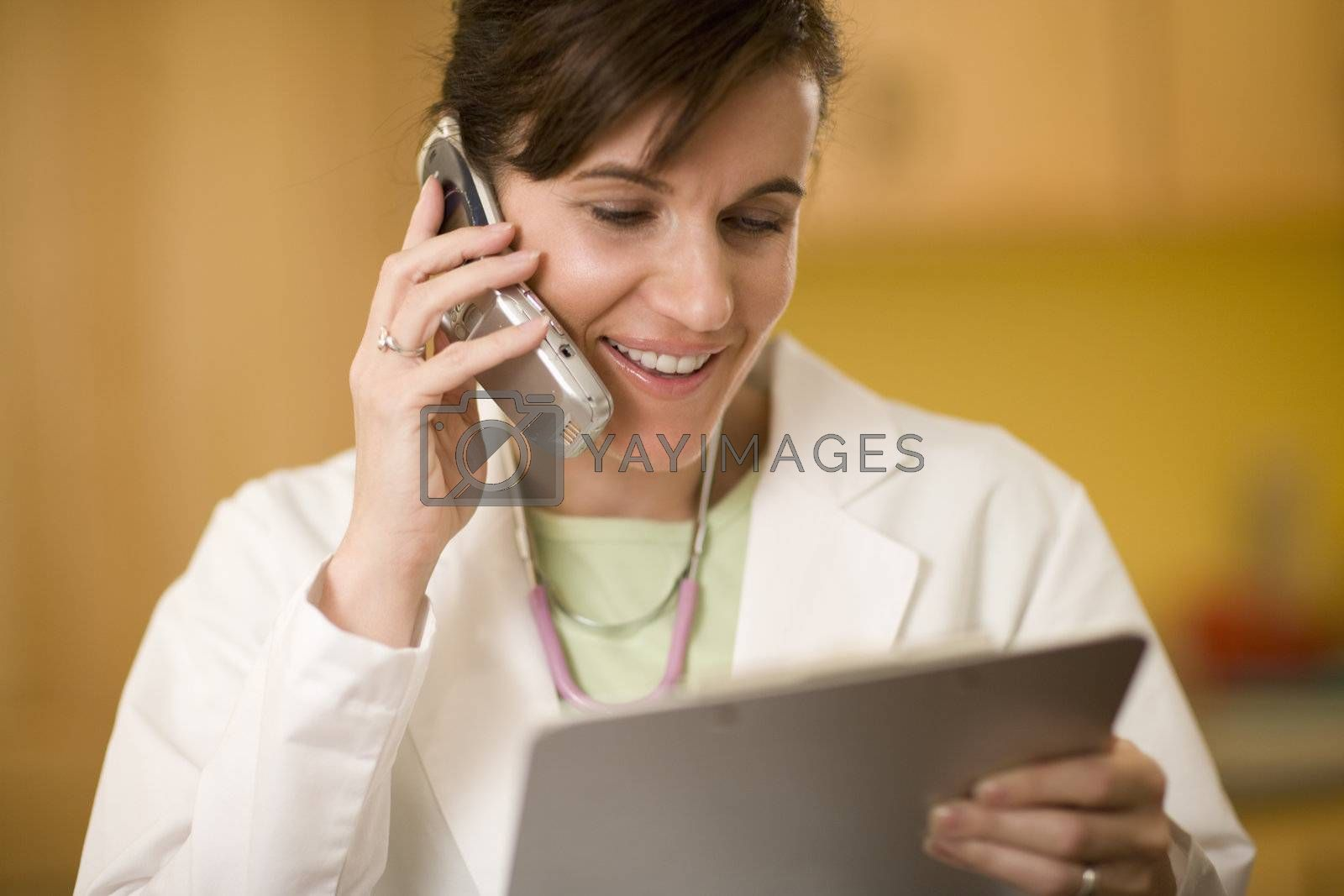 Doctor on phone reading medical records by edbockstock