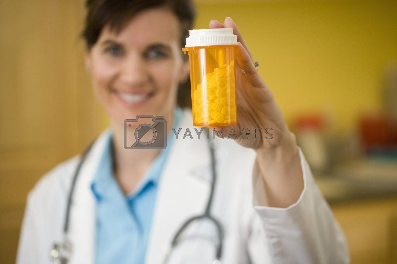 Female Physician holding bottle of pills up to camera, focus on pills