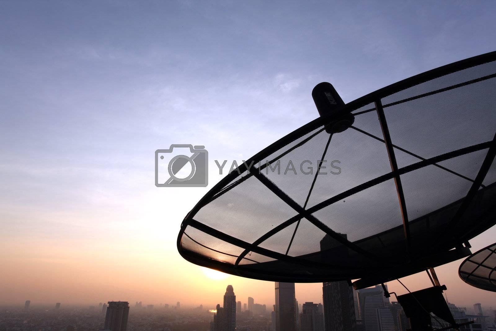 black antenna communication satellite dish over sunset sky in city